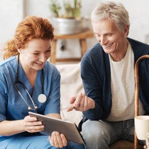 nurse and senior looking at tablet